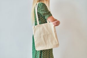 A Girl is holding blank cotton eco tote bag, design mockup.
