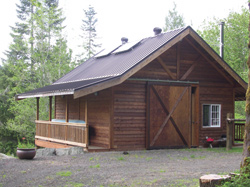 """The Lees' off the grid cabin and barn in Washington""""s Olympic Peninsula get power from two small solar panels. © Kathy Lee"""